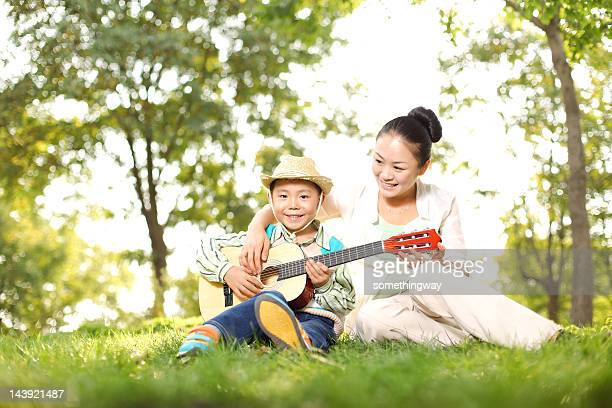 Mother and son playing guitar in the park
