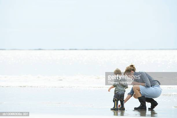 Mother and son (15-18 months) playing on shore, side view