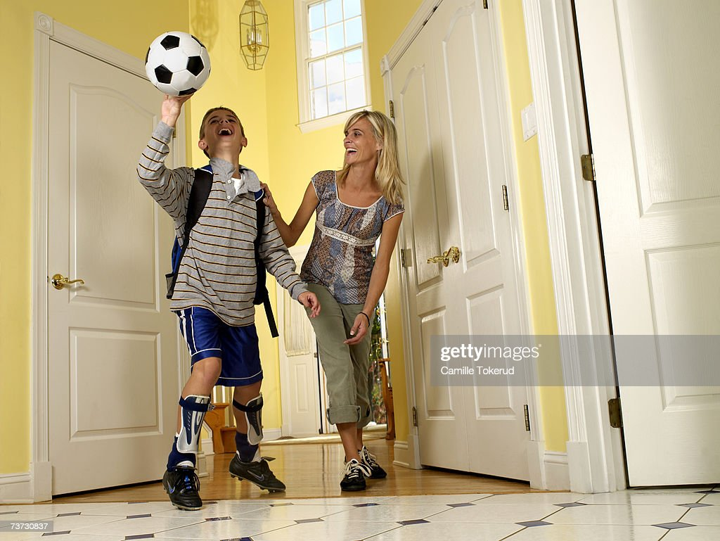 Mother and son (8-10) playing with football in doorway at home