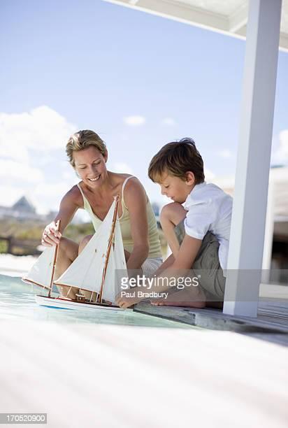 Mère et son fils jouant dans la piscine avec Bateau miniature