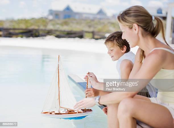 Mutter und Sohn spielen mit einem Miniatur-Boot im pool