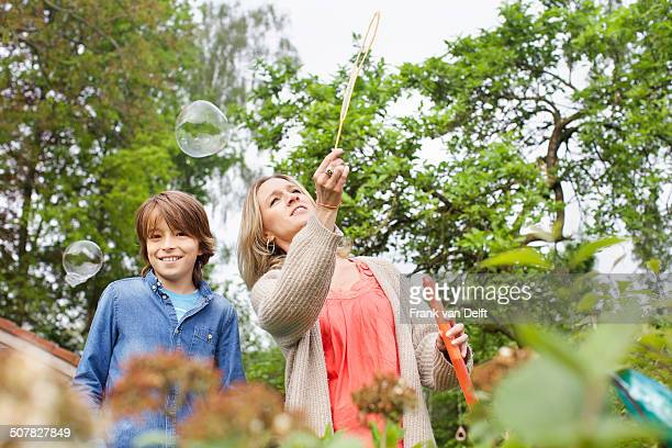 Mother and son playing with soap bubbles in garden
