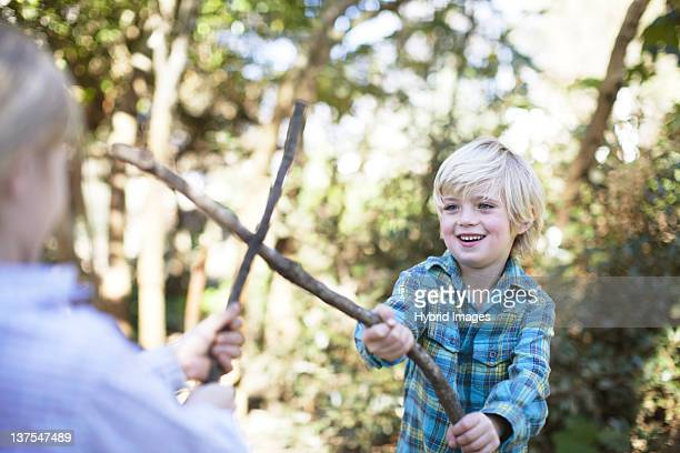 Mother and son playing with sticks