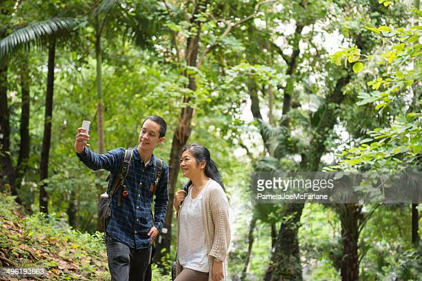 Mother and Son Posing for Selfie in a Forest