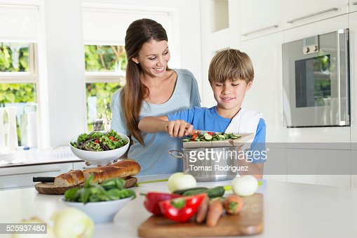 Mother and son (6-7) preparing food in kitchen : Bildbanksbilder