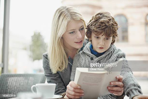 Mother and son reading book in a café