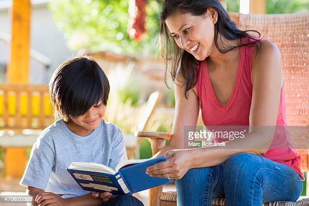 Mother and son reading together on porch