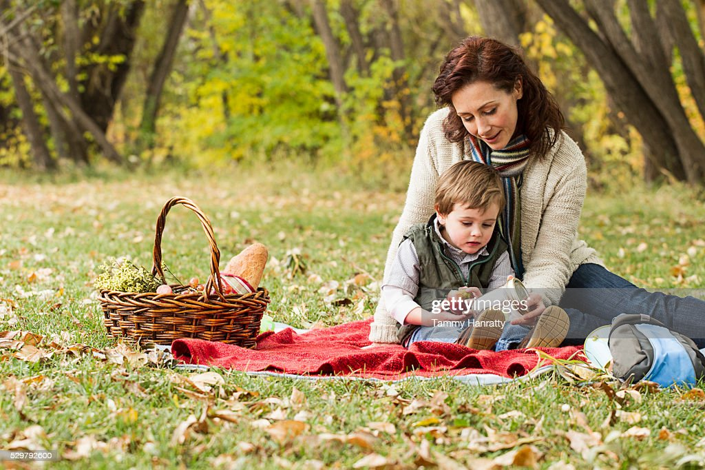 Mother and son (4-5) relaxing on ground : Foto de stock