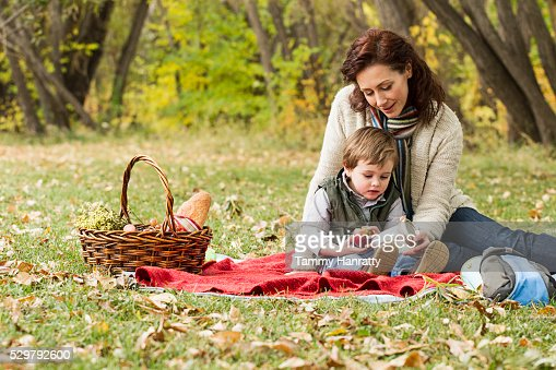 Mother and son (4-5) relaxing on ground : Stock Photo