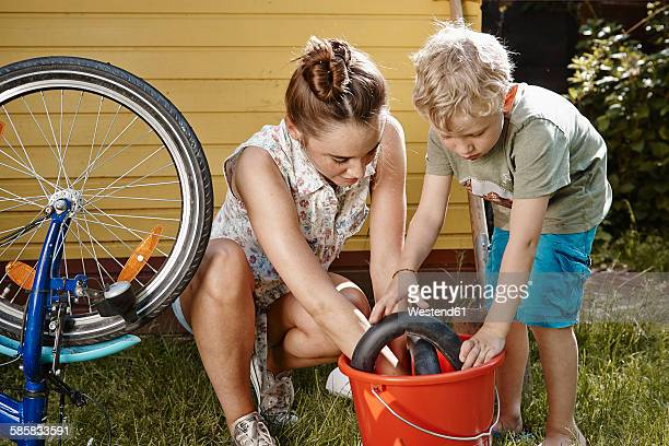 Mother and son repairing bicycle together