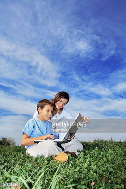 Mother and son resting outdoor with laptop