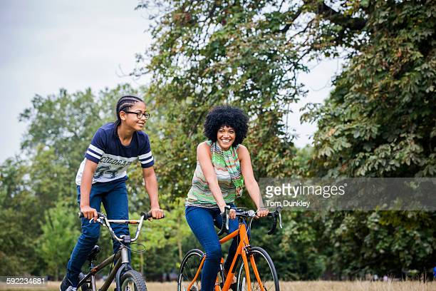 Mother and son riding on bicycles smiling
