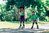 Mother and son roller skating in park