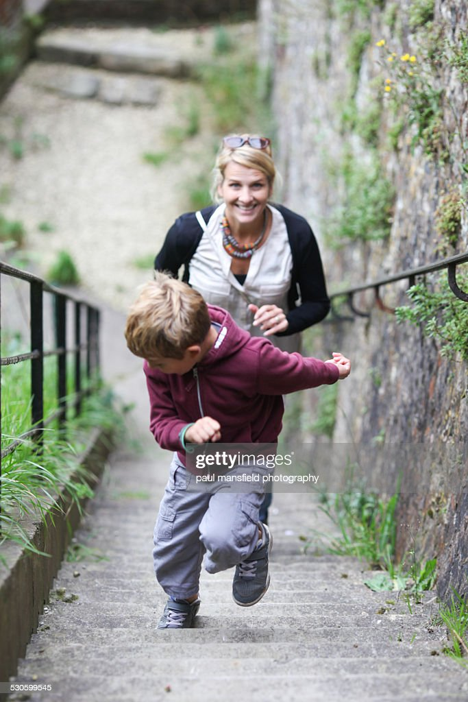 Mother and son running up a staircase : Stock Photo