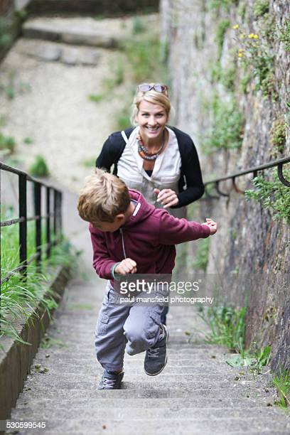 Mother and son running up a staircase