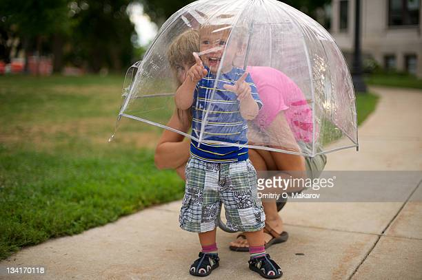 Mother and son seeing through umbrella