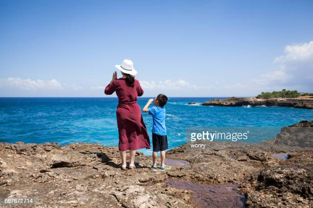 Mother and son shouting on cliff