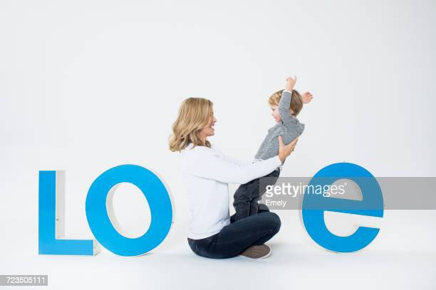 Mother and son sitting between three-dimensional letters, creating the word LOVE