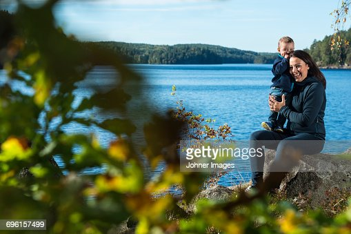 Mother and son sitting by lake