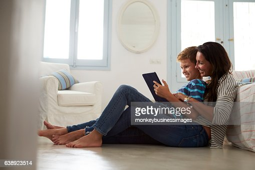 Mother And Son Sitting On Floor Using Digital Tablet : Stock Photo