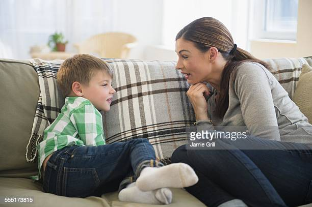 Mother and son (6-7) sitting on sofa