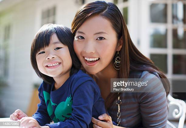 Mother and son sitting together outdoors
