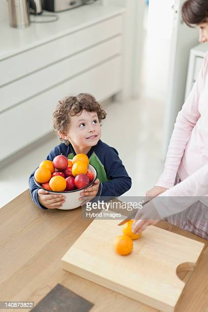 Mother and son slicing fruit in kitchen