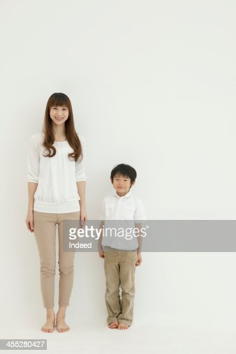 Mother and son smile in front of the white background