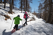 Young woman and her little son snowshoeing in a sunny day
