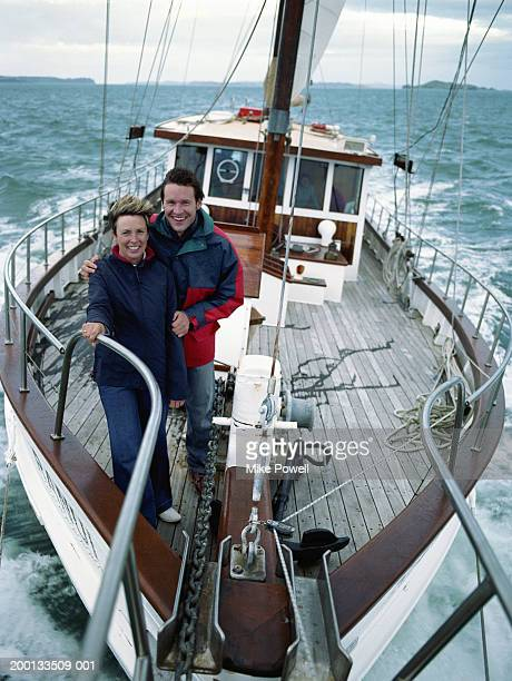 Mother and son standing on bow of sailboat, portrait