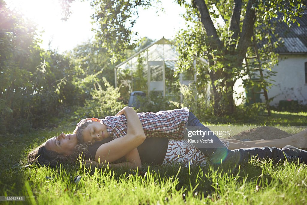 Mother and son taking a nap in their green garden : Stock Photo