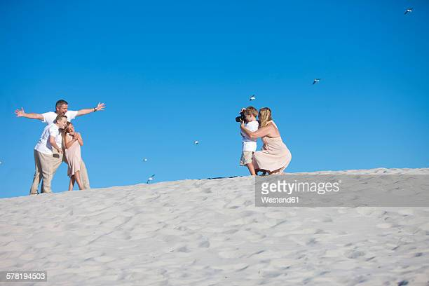 Mother and son taking a picture of father and children on a sandy beach