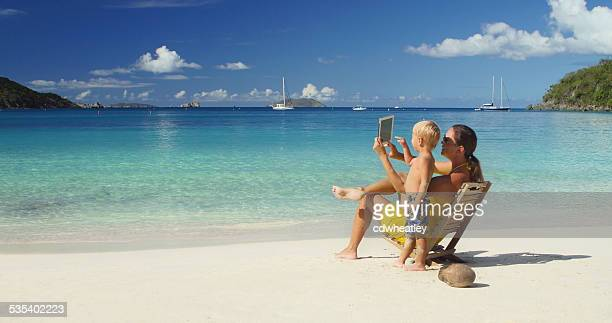 mother and son taking photographs with tablet at the beach
