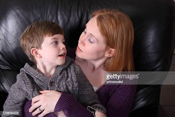 Mother and son talking while lying on leather sofa
