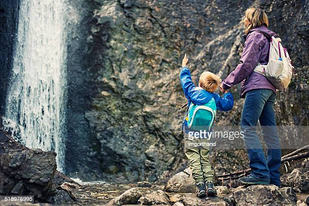 Mother and son trekking by the waterfall