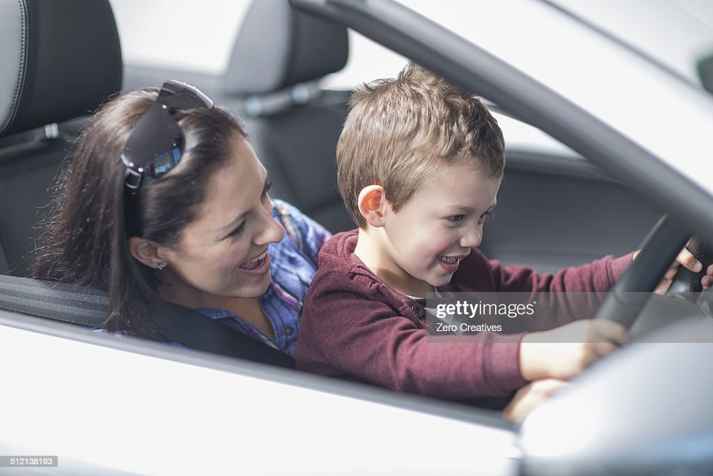 Mother and son trying out new car in car dealership