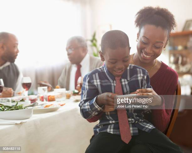 Mother and son using cell phone at holiday table