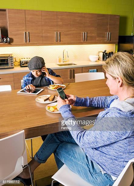 Mère et fils à l'aide d'appareils numériques sur le cuisine Tableau