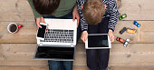 Top view image of young kid and his mother using online media Laptop, smartphone and digital tablet. Concept of mobile addiction.