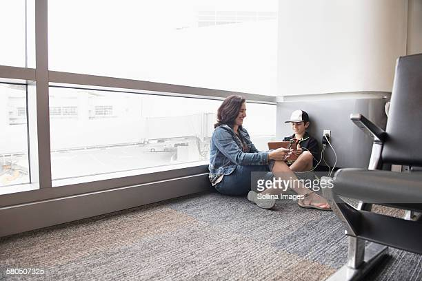Mother and son using digital tablet in airport