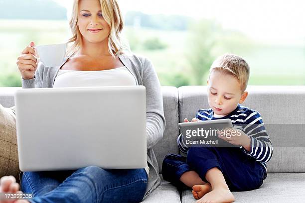 Mother and son using electronic devices