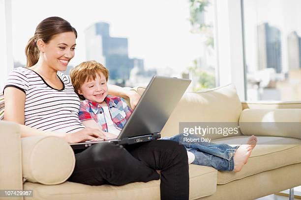 Mutter und Sohn mit laptop im Wohnzimmer