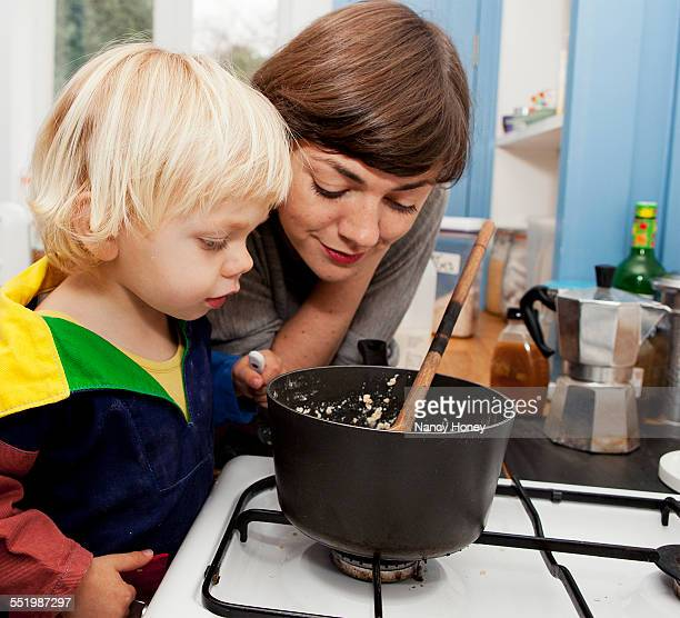 Mother and son waiting for porridge to cook in kitchen