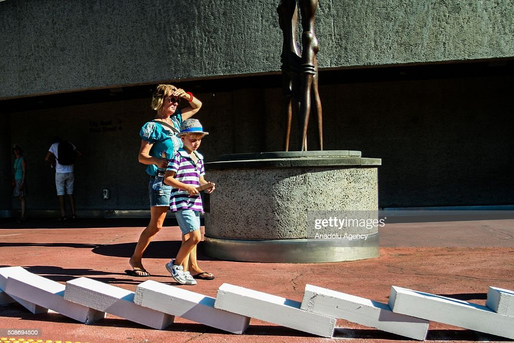 A mother and son walk past collapsed dominoes during the Arts Centre Melbournes Dominoes arts project in Melbourne, Australia February 6, 2016. More than 7000 giant dominoes snaked through Melbourne city over 2km.