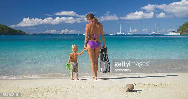 mother and son walking along the beach with snorkeling gear