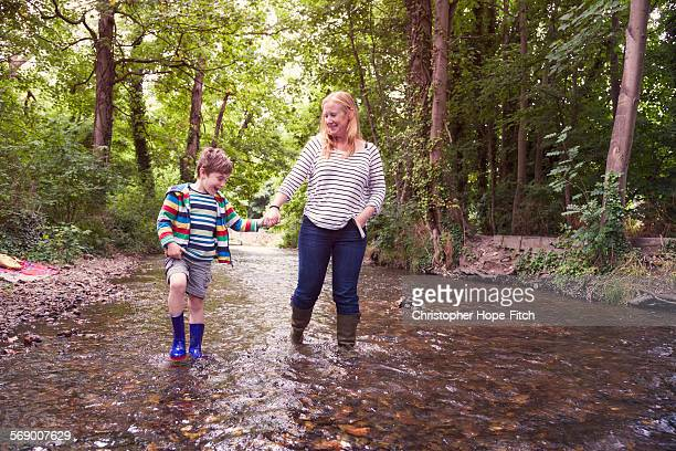 Mother and son walking in a river