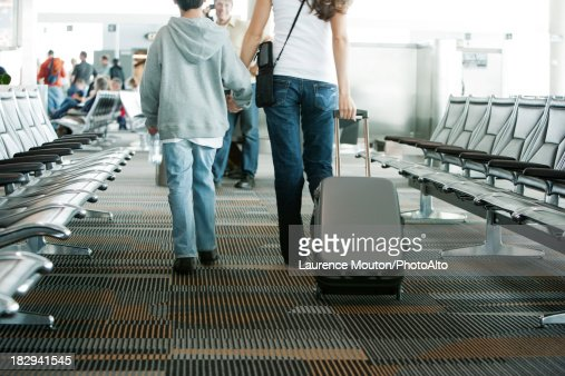 Mother And Son Walking In Airport Mother Pulling Suitcase
