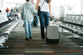 Mother and son walking in airport, mother pulling suitcase, rear view
