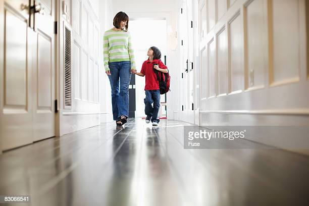 Mother and Son Walking in Hallway