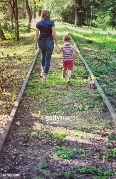 Madre e figlio a piedi su un abbandonato binario.